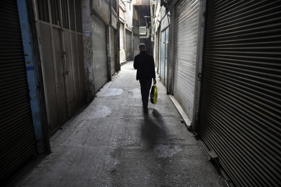 A man walks through closed Tehran's Grand Bazaar, Iran, Saturday, April 10, 2021. Iran on Saturday imposed partial lockdown on businesses in major shopping centers as well as intercity travels through personal cars in major cities including capital Tehran as it struggles with the worst outbreak of the coronavirus in the Mideast region. (AP Photo/Vahid Salemi)