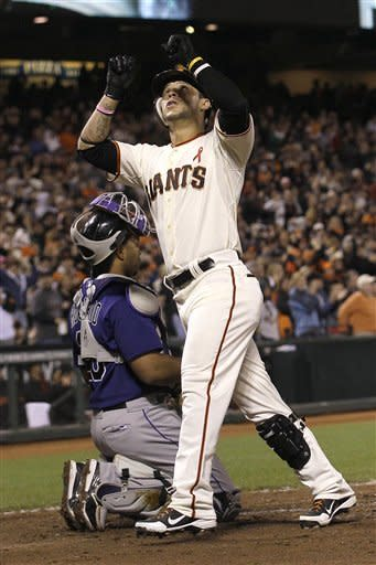 San Francisco Giants' Gregor Blanco, foreground, celebrates in front of Colorado Rockies catcher Wilin Rosario after hitting a solo home run off of pitcher Christian Friedrich during the sixth inning of a baseball game in San Francisco, Monday, May 14, 2012. (AP Photo/Jeff Chiu)