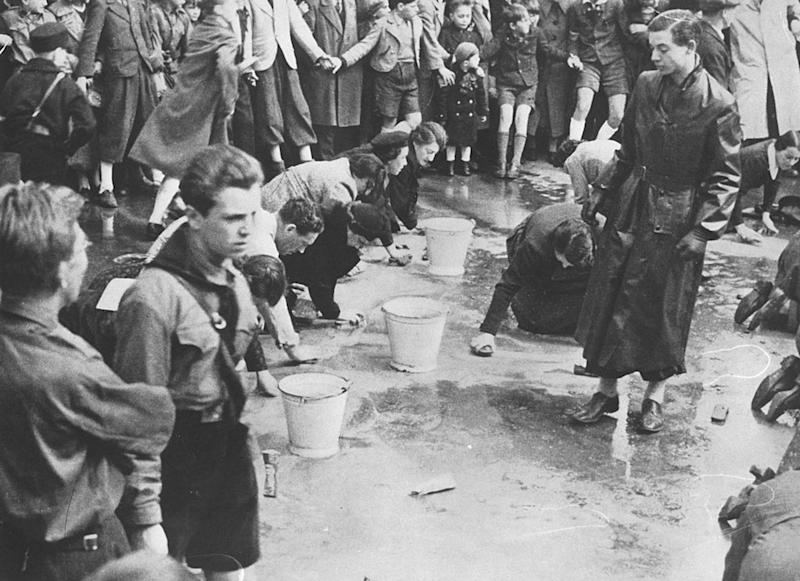 A 1938 photo of Hitler Youth members looking on as Jewish people were forced to scrub the streets in Vienna, Austria. | Universal History Archive/Universal Images Group—Getty Images