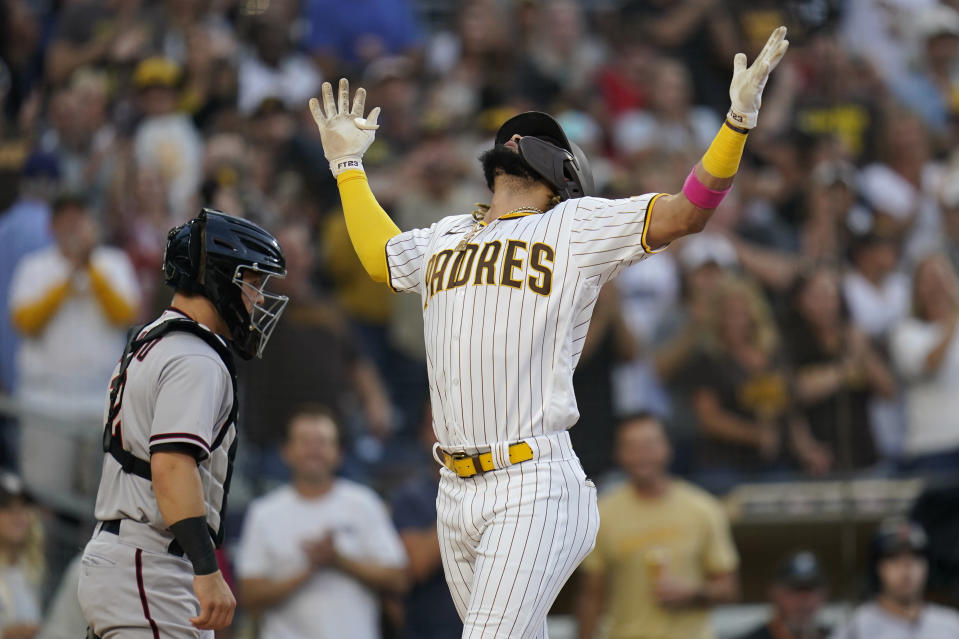 San Diego Padres' Fernando Tatis Jr., right, reacts after hitting a home run during the first inning of a baseball game as Arizona Diamondbacks catcher Daulton Varsho looks on Friday, June 25, 2021, in San Diego. (AP Photo/Gregory Bull)