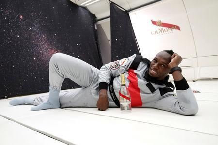 """Retired sprinter Usain Bolt poses with a bottle of """"Mumm Grand Cordon Stellar"""" champagne as he enjoys zero gravity conditions during a flight in a specially modified Airbus Zero-G plane above Reims, France, September 12, 2018. REUTERS/Benoit Tessier"""