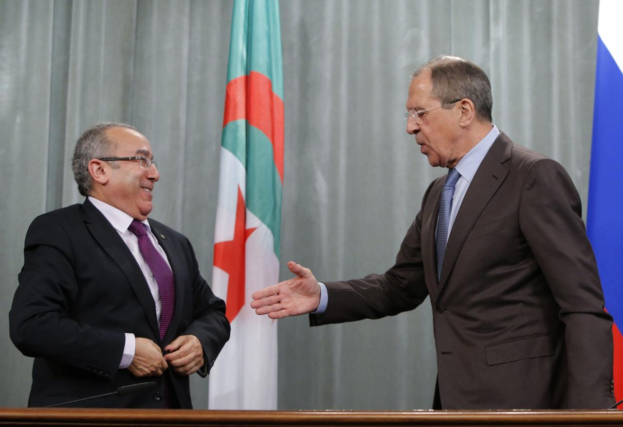 Russia's Foreign Minister Sergei Lavrov (R) shakes hands with his Algerian counterpart Ramtane Lamamra during a news conference in Moscow February 11, 2014. Lavrov said on Tuesday that a draft U.N. Security Council resolution aimed boost aid access to Syria was one-sided and detached from reality, the Interfax news agency reported. REUTERS/Maxim Shemetov (RUSSIA - Tags: POLITICS)