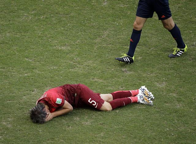 Portugal's Fabio Coentrao grimaces in pain after being injured during the group G World Cup soccer match between Germany and Portugal at the Arena Fonte Nova in Salvador, Brazil, Monday, June 16, 2014. (AP Photo/Christophe Ena)