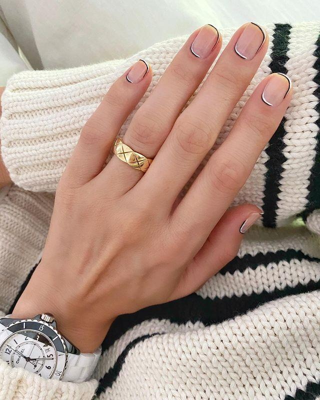 "<p>I mean, how chic is this black and white <a href=""https://www.cosmopolitan.com/style-beauty/beauty/a8484260/new-years-eve-nail-designs/"" rel=""nofollow noopener"" target=""_blank"" data-ylk=""slk:nail design"" class=""link rapid-noclick-resp"">nail design</a>? You'll need a <a href=""https://www.amazon.com/Winstonia-Striping-Striper-Acrylic-Handle/dp/B00GU0OYK6/ref=sr_1_3?tag=syn-yahoo-20&ascsubtag=%5Bartid%7C10049.g.34702993%5Bsrc%7Cyahoo-us"" rel=""nofollow noopener"" target=""_blank"" data-ylk=""slk:thin striping brush"" class=""link rapid-noclick-resp"">thin striping brush</a> (it's a must for creating precise, ultra-fine lines), <a href=""https://www.amazon.com/OPI-Nail-Lacquer-Black-Onyx/dp/B000NG4778/ref=sr_1_5?tag=syn-yahoo-20&ascsubtag=%5Bartid%7C10049.g.34702993%5Bsrc%7Cyahoo-us"" rel=""nofollow noopener"" target=""_blank"" data-ylk=""slk:black nail polish"" class=""link rapid-noclick-resp"">black nail polish</a>, and opaque <a href=""https://www.amazon.com/OPI-Infinite-Shine-Funny-Bunny/dp/B004NMT926/ref=sr_1_2_sspa?tag=syn-yahoo-20&ascsubtag=%5Bartid%7C10049.g.34702993%5Bsrc%7Cyahoo-us"" rel=""nofollow noopener"" target=""_blank"" data-ylk=""slk:white nail polish"" class=""link rapid-noclick-resp"">white nail polish</a> to DIY the trendy look.</p><p><a href=""https://www.instagram.com/p/CFaBREnlj52/?utm_source=ig_embed&utm_campaign=loading"" rel=""nofollow noopener"" target=""_blank"" data-ylk=""slk:See the original post on Instagram"" class=""link rapid-noclick-resp"">See the original post on Instagram</a></p>"