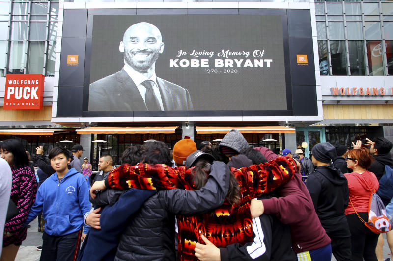 Fans of Kobe Bryant mourn in front of his image at the LALive area across from Staples Center, home of the Los Angeles Lakers, after word of the Lakers star's death in a helicopter crash, in downtown Los Angeles Sunday, Jan. 26, 2020. (AP Photo/Matt Hartman)