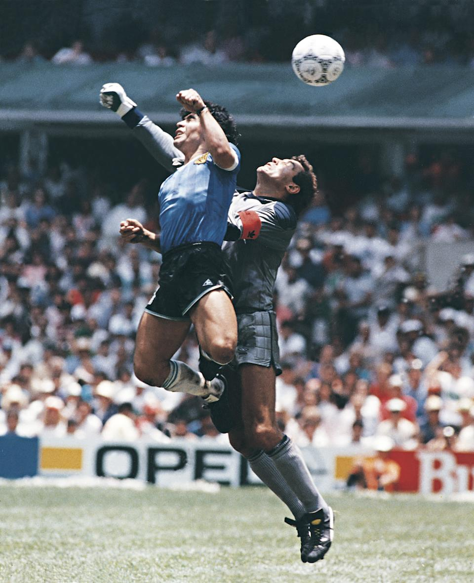 MEXICO CITY, MEXICO - JUNE 22: Diego Maradona of Argentina uses his hand to score the first goal of his team during a 1986 FIFA World Cup Quarter Final match between Argentina and England at Azteca Stadium on June 22, 1986 in Mexico City, Mexico. Maradona later claimed that the goal was scored by 'The Hand Of God'. (Photo by Archivo El Grafico/Getty Images)