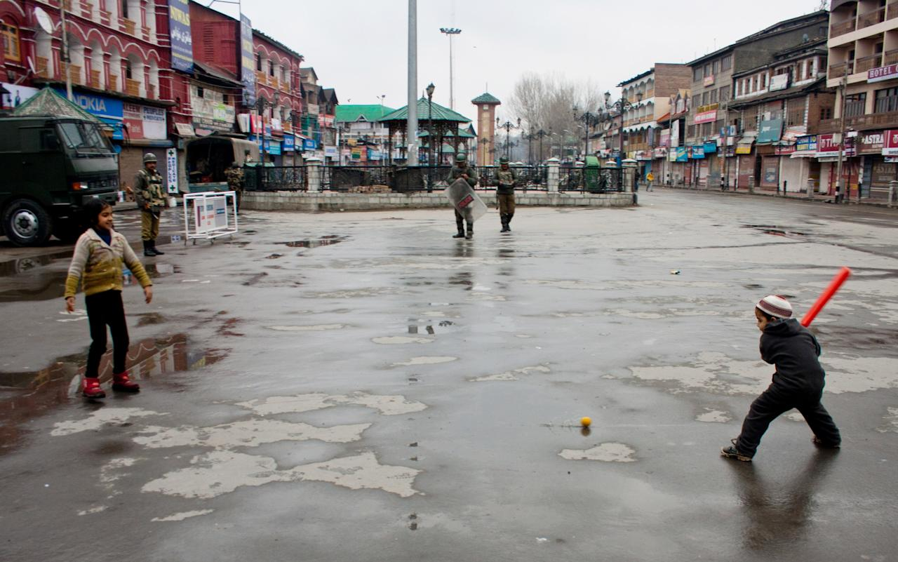 SRINAGAR, KASHMIR, INDIA - FEBRUARY 15: Kashmir Muslim children play cricket as Indian paramilitary soldiers patrol streets in city centre during a strict curfew on the seventh consecutive day, imposed after the execution of alleged Indian parliament attacker Mohammad Afzal Guru on February 15, 2013 in Srinagar, the summer capital of Indian Administered Kashmir, India. Afzal Guru, from Sopore town in the north of Kashmir, was hung on February 09 for his role in the 2001 Indian parliament attack which left 14 dead. The hanging has further strained relations between India - who blamed the attack on 'Pakistan backed' militant group Jaish-e-Mohammed - and neighbouring Pakistan and has seen an military increase from both along the border.Curfew was lifted from some parts of Srinagar after four days.  (Photo by Yawar Nazir/Getty Images)