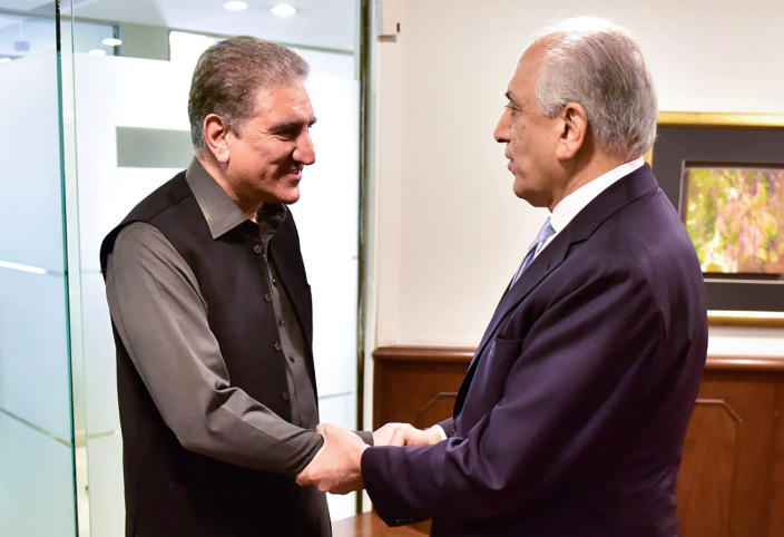 In this photo released by the Foreign Office, Pakistan's Foreign Minister Shah Mehmood Qureshi, left, meets U.S. envoy Zalmay Khalilzad at the Foreign Ministry in Islamabad, Pakistan, Friday, Jan. 31, 2020. Khalilzad has met with Pakistan's foreign minister to find a peaceful solution to neighboring Afghanistan's war. (Pakistan Foreign Office via AP)
