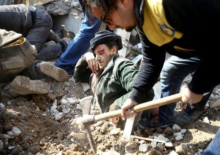 A man gets stuck under debris at a damaged site after an airstrike in the Saqba area, in the eastern Damascus suburb of Ghouta, Syria January 9, 2018. REUTERS/Bassam Khabieh/File photo