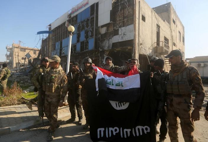 Iraqi security forces place the Iraqi flag above the Islamic State group flag on December 28, 2015 in front of the Anbar police headquarters after they recaptured Ramadi (AFP Photo/Ahmad al-Rubaye)