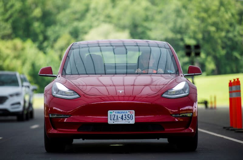 FILE PHOTO: IIHS media relations associate Young demonstrates front crash prevention test on Tesla Model 3 at IIHS-HLDI Vehicle Research Center in Ruckersville, Virginia