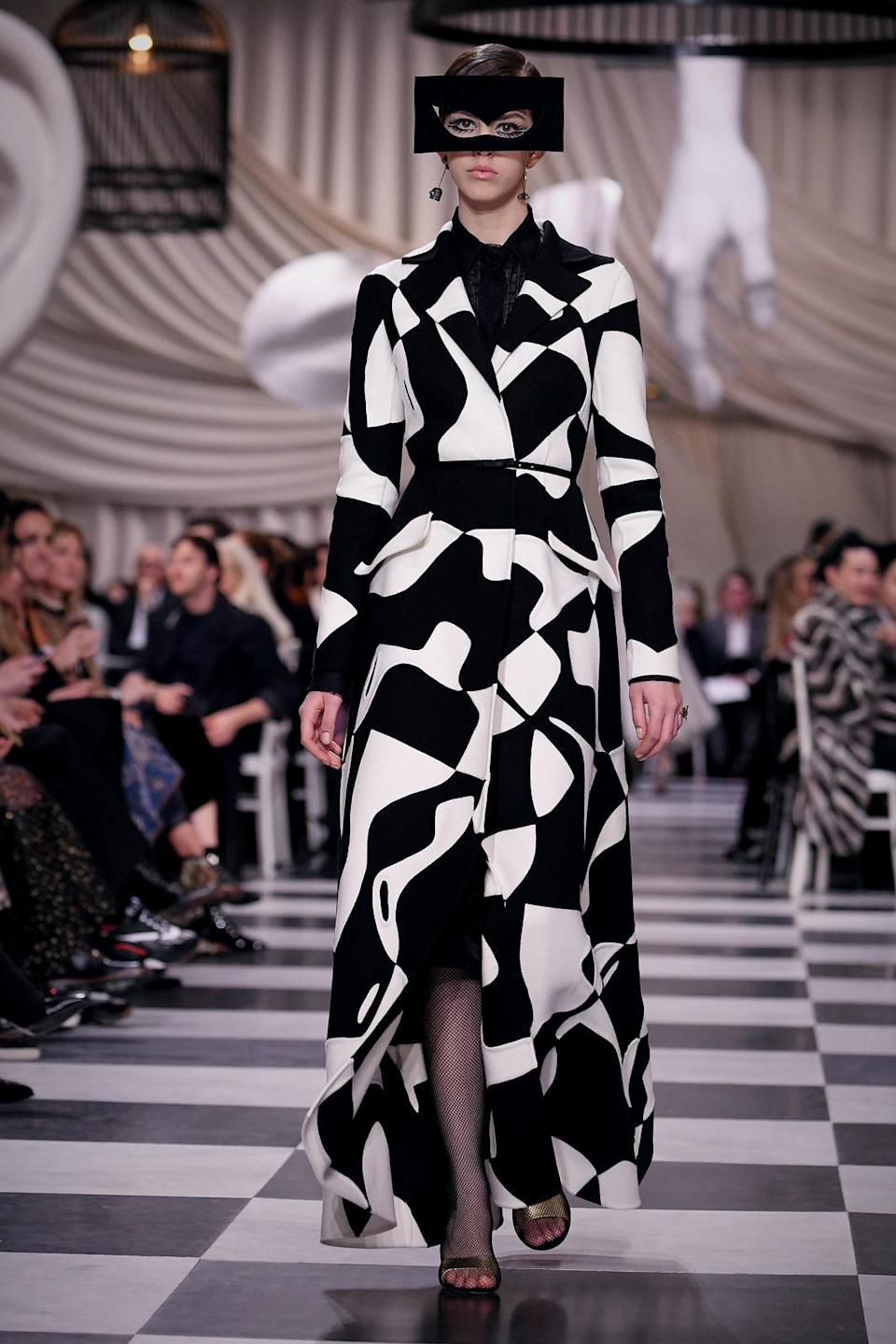 "<p>A model wears a black and white ""puzzle"" coat and cut-out mask from the Dior Haute Couture SS18 collection. (Photo: Getty) </p>"