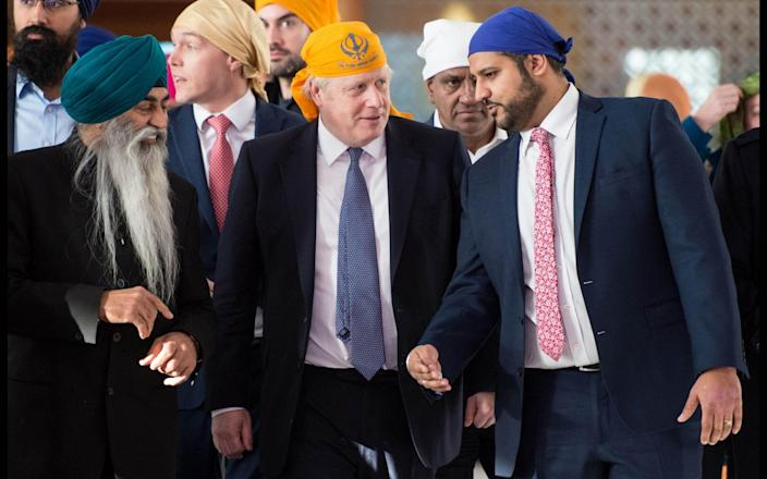 Boris Johnson visits a Sikh temple in London with Samir Jassal (right) - Pete Maclaine / i-Images