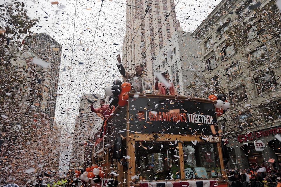 San Francisco Giants manager Bruce Bochy, top center, waves as he carries the 2014 World Series trophy during the victory parade for baseball's 2014 World Series champions, Friday, Oct. 31, 2014, in San Francisco. (AP Photo/Marcio Jose Sanchez)