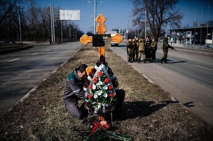 A man fixes a wooden cross in memory of fallen pro-Russian separatist soldiers near Donetsk airport on March 21, 2015 (AFP Photo/Dimitar Dilkoff)
