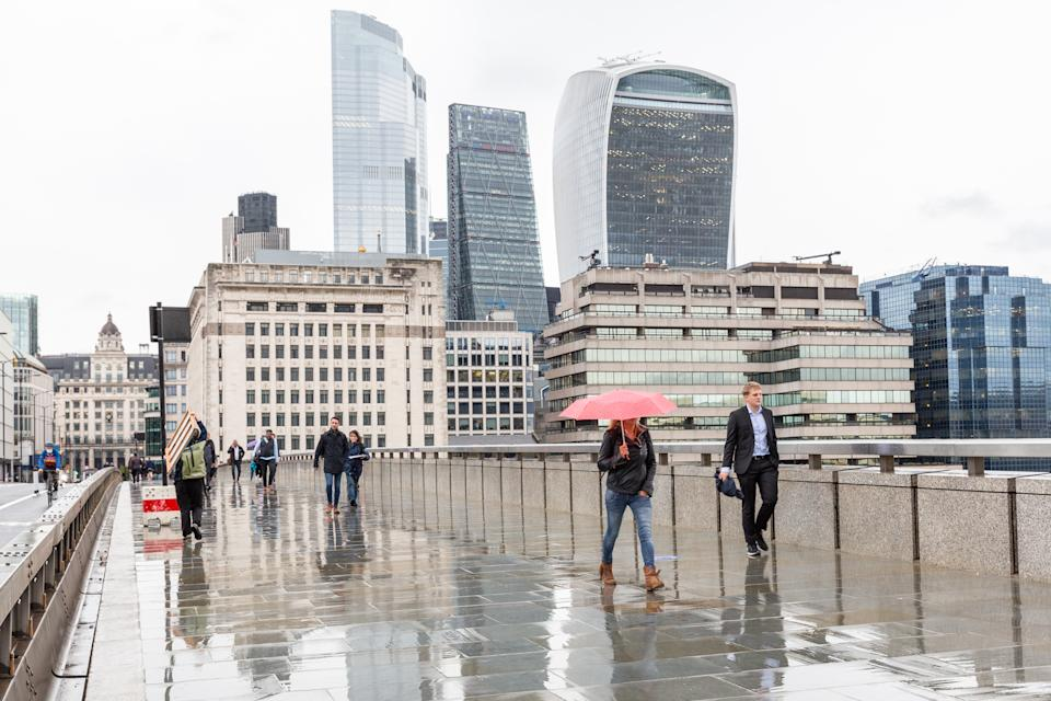 Pedestrians are seen on a rainy afternoon walking down London Bridge sideway by the City of London. (Credit: Dominika Zarzycka/NurPhoto)