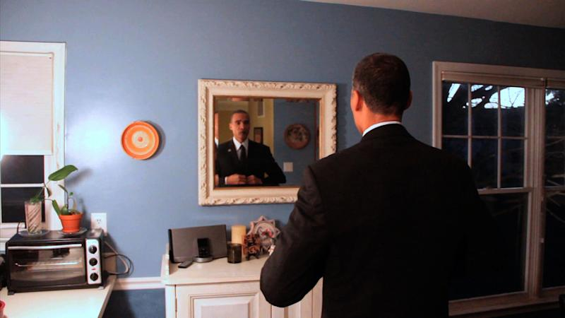 """In this image from video, President Barack Obama lookalike Larry Graves gets ready for an appearance. Graves has the security detail, the prominent ears and the U.S. flag pin, but substitute teacher Graves is no Barack Obama. He's a professional lookalike for the president. They have something else in common, too: a frantic schedule leading up to the inauguration. """"It's definitely a busy time,"""" Graves said. """"Between the campaign season and the inauguration, it's been prime time. Barack Obama is a respectable guy. People want to have him at their parties."""" (AP Photo)"""
