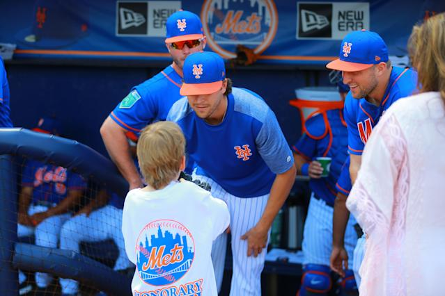 <p>New York Mets pitcher Jacob deGrom and outfielder Tim Tebow listen to a young fan before the baseball game against the Miami Marlins at First Data Field in Port St. Lucie, Fla., March 1, 2018. (Photo: Gordon Donovan/Yahoo News) </p>
