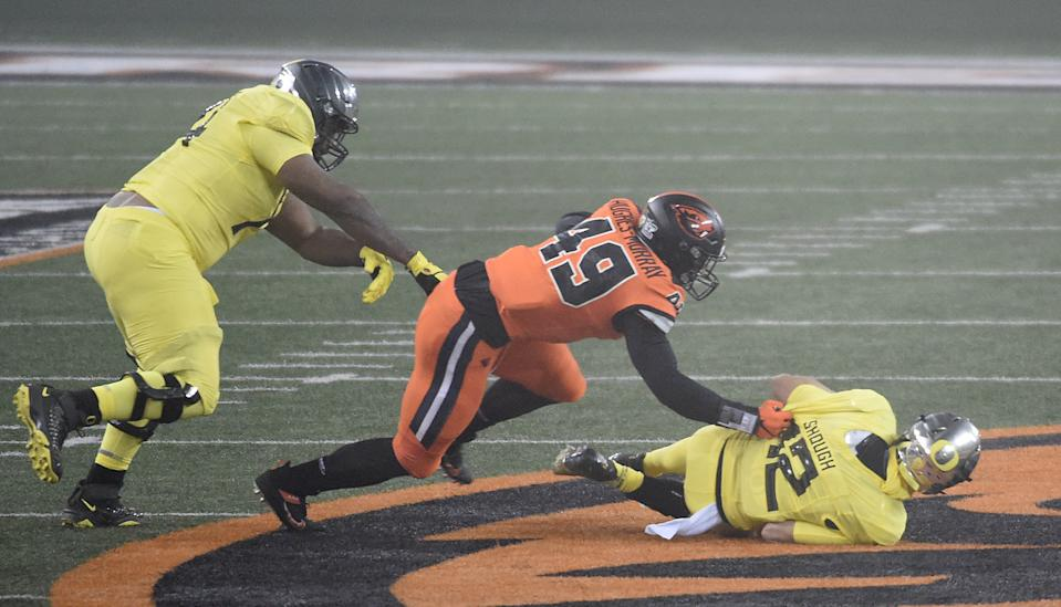 CORVALLIS, OREGON - NOVEMBER 27: Linebacker Andrzej Hughes-Murray #49 of the Oregon State Beavers sacks Quarterback Tyler Shough #12 of the Oregon Ducks during the first half of the game at Reser Stadium on November 27, 2020 in Corvallis, Oregon. (Photo by Steve Dykes/Getty Images)
