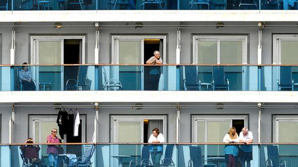 PHOTO: Passengers look out from balconies aboard the Grand Princess cruise ship as it maintains a holding pattern about 25 miles off the coast of San Francisco, California, on March 8, 2020. (Noah Berger/AP)