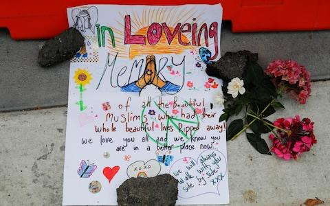 A message is displayed at a makeshift memorial outside Christchurch hospital in Christchurch, New Zealand - Credit: AP