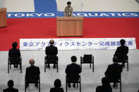 Tokyo Gov. Yuriko Koike, center top, delivers opening remarks during a grand opening ceremony of Tokyo Aquatics Center Saturday, Oct. 24, 2020, in Tokyo. The Tokyo 2020 organizing committee held the grand opening ceremony Saturday at the aquatics center, planned to host Olympic artistic swimming, diving and swimming and Paralympics swimming events in 2021. (AP Photo/Eugene Hoshiko)