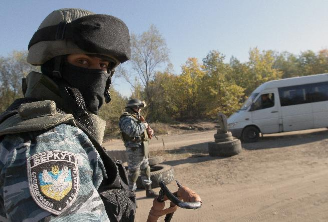 Police officers wearing uniforms of the now-disbanded Ukrainian Berkut special forces stand guard at a checkpoint near Schastya in the Lugansk region of eastern Ukraine on October 11, 2014 (AFP Photo/Anatolii Boiko)