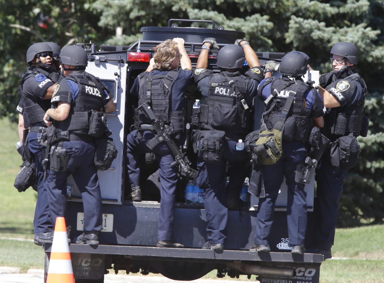 Police personnel move outside the Sikh Temple in Oak Creek, Wis, where a shooting took place Sunday, Aug. 5, 2012. (AP Photo/Jeffrey Phelps)