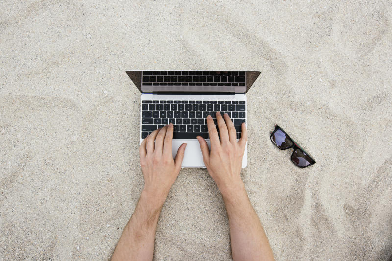 Man hands using laptop with sunglasses near it on a sandy beach, shot directly from above in South Beach, Miami, Florida, USA.