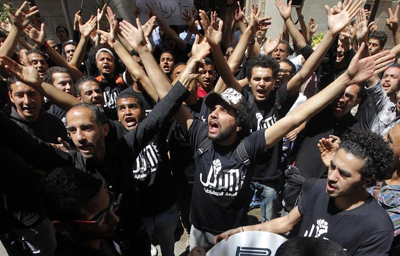 "Members of Egypt's April 6 Youth Movement shout anti-Muslim Brotherhood slogans during a rally in front of Cairo's stock market, in Cairo, Egypt, Saturday, April 6, 2013. The group is rallying to mark its fifth anniversary and to protest against President Mohammed Morsi. Arabic on T-shirts reads, ""6th April."" (AP Photo/ Amr Nabil)"