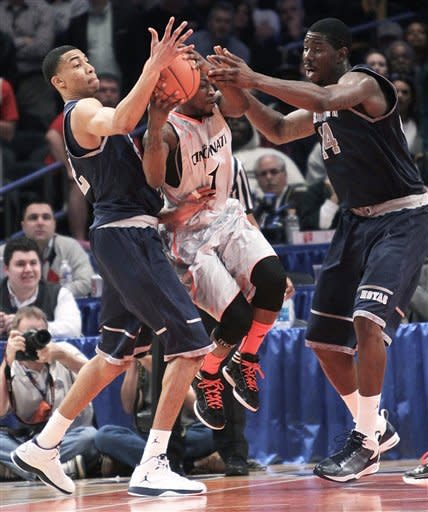 Cincinnati's Cashmere Wright, center, is double-teamed by Georgetown's Otto Porter, left, and Henry Sims during an NCAA college basketball game in the quarterfinals of the Big East Conference tournament in New York, Thursday, March 8, 2012. Cincinnati beat Georgetown in double overtime 72-70. (AP Photo/Seth Wenig)