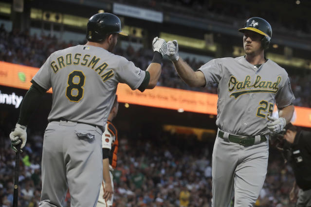 Oakland Athletics' Stephen Piscotty, right, is congratulated by Robbie Grossman after hitting a solo home run against the San Francisco Giants during the fifth inning of a baseball game in San Francisco, Tuesday, Aug. 13, 2019. (AP Photo/Jeff Chiu)