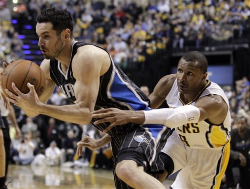 Indiana Pacers guard Leandro Barbosa, right, reaches around Orlando Magic guard J.J. Redick who drives in the first half of an NBA first-round playoff basketball game in Indianapolis, Saturday, April 28, 2012. (AP Photo/Michael Conroy)