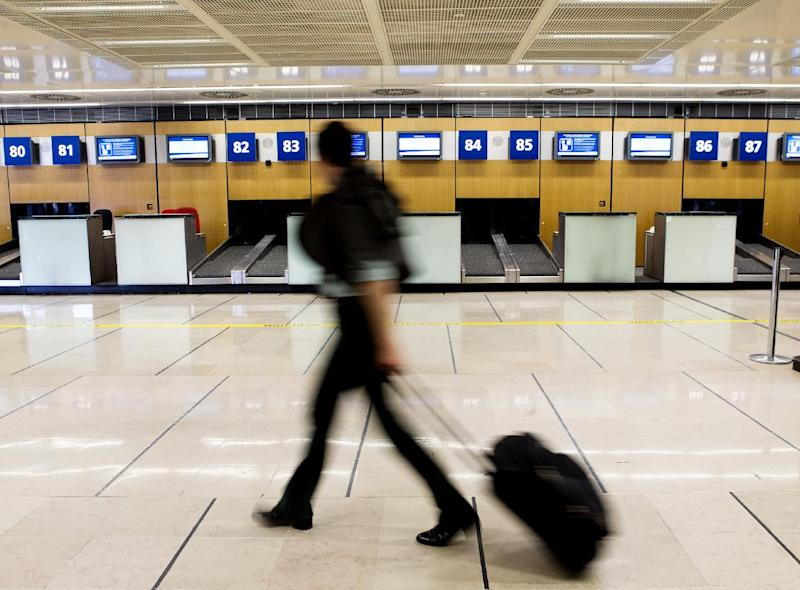 A passenger walks past vacant check in desks at Orly airport, west of Paris, France, during a strike by French air traffic controllers, Tuesday, June 11, 2013. Airlines have slashed flights in France as a strike by air traffic controllers fearful of a plan to unify European skies went into full force Tuesday. France's main airports have cut their flight timetables in half to cope with a three-day strike by air traffic controllers.(AP Photo/Jacques Brinon)