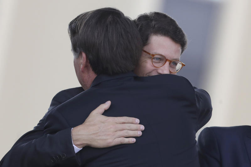 FILE - In this Aug. 23, 2019 file photo, Brazilian President Jair Bolsonaro, back, embraces his Environment Minister Ricardo Salles during a military ceremony for the Day of the Soldier at the army headquarters in Brasilia, Brazil. Amidst a broader government effort to slash public spending, Salles announced in April a 24% budget cut for Ibama, the government's Brazilian Institute of the Environment and Renewable Natural Resource, which carries out on-the-ground operations tackling environmental crime in hot spots identified through a mix of intelligence and satellite images. (AP Photo/Eraldo Peres, File)