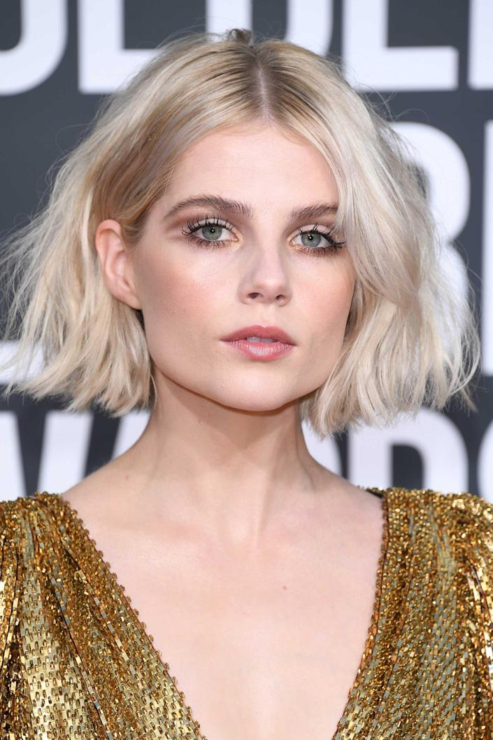 """There are warm undertones in Lucy Boynton's complexion, which means silvery, near-white blonde hair works as a cool counterpoint. """"The blue in Lucy's eyes complement her silver-toned blonde hair quite well,"""" adds Miller. """"Because Lucy has depth at her base, it breaks up the ash tones in her hair keeping her from looking washed out."""" Because her roots are left natural and dark, the overall effect is less shocking and more organic. Keeping your brows dark is an excellent choice — your features will appreciate the grounding effect."""