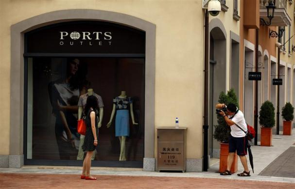 A man takes a photograph of a woman outside a fashion store in the Florentia Village in the district of Wuqing, located on the outskirts of the city of Tianjin June 13, 2012.