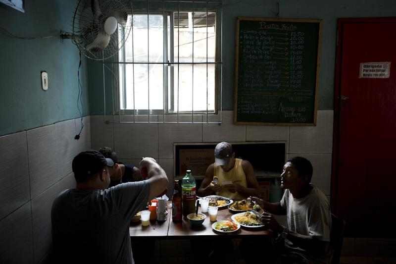 In this May 22, 2013 photo, customers eat lunch at Restaurante 48 in the Tabajaras slum in Rio de Janeiro, Brazil. The pacified favelas are the newest hotspots for both locals and foreign visitors, including a number of bars and restaurants. (AP Photo/Victor R. Caivano)