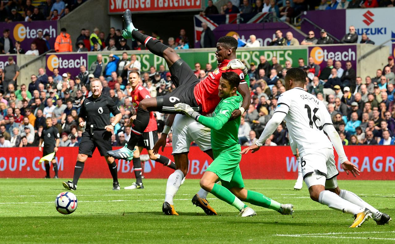 """Soccer Football - Premier League - Swansea City vs Manchester United - Swansea, Britain - August 19, 2017   Swansea City's Lukasz Fabianski collides with Manchester United's Paul Pogba    REUTERS/Rebecca Naden     EDITORIAL USE ONLY. No use with unauthorized audio, video, data, fixture lists, club/league logos or """"live"""" services. Online in-match use limited to 45 images, no video emulation. No use in betting, games or single club/league/player publications. Please contact your account representative for further details.     TPX IMAGES OF THE DAY"""