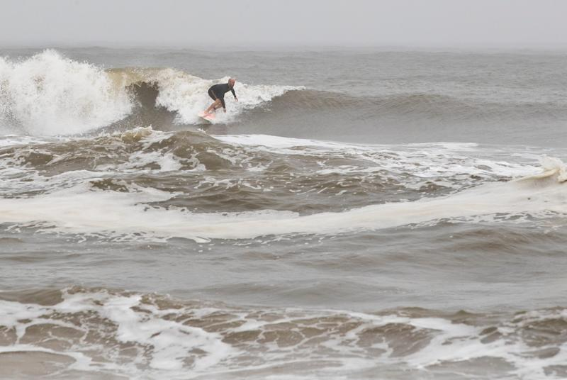 A surfer finds a wave in Mexico Beach, Fla. after Tropical Storm Nestor hit the town on Saturday, Oct. 19, 2019. The storm brought heavy rain and high surf, but did not damage the town severely.