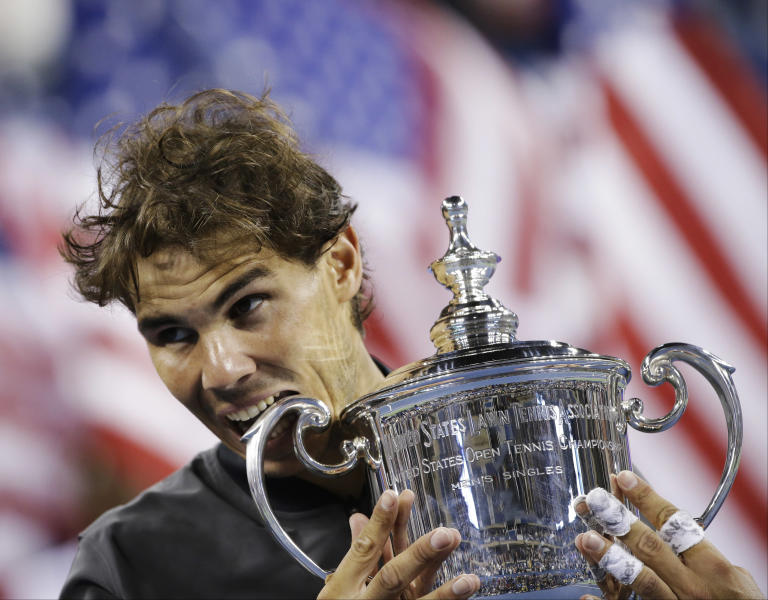 Rafael Nadal, of Spain, bites the trophy while posing for photos after defeating Novak Djokovic, of Serbia, during the men's singles final of the 2013 U.S. Open tennis tournament, Monday, Sept. 9, 2013, in New York. (AP Photo/David Goldman)