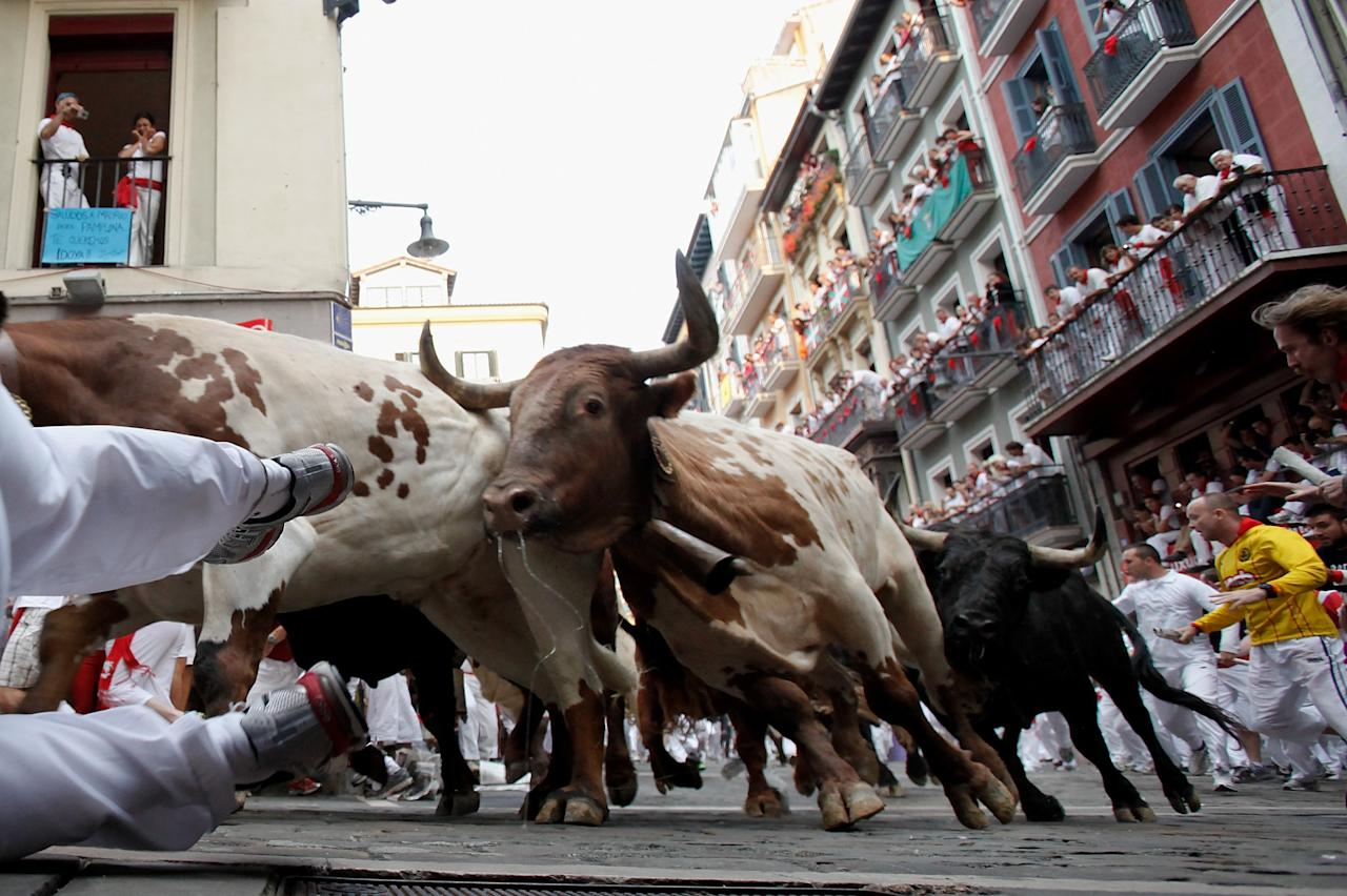 PAMPLONA, SPAIN - JULY 12: A reveller falls running with El Pilar's ranch fighting bulls at Curva Estafeta during the seventh day of the San Fermin Running Of The Bulls festival on July 12, 2013 in Pamplona, Spain. The annual Fiesta de San Fermin, made famous by the 1926 novel of US writer Ernest Hemmingway 'The Sun Also Rises', involves the running of the bulls through the historic heart of Pamplona, this year for nine days from July 6-14. (Photo by Pablo Blazquez Dominguez/Getty Images)