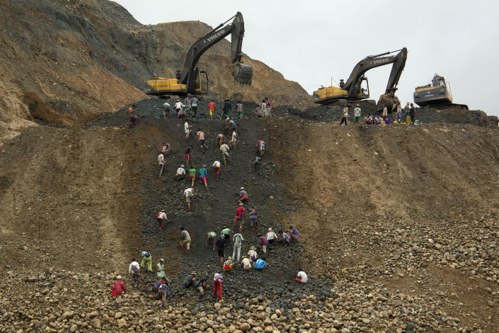 FILE - In this June 15, 2015, file photo, freelance jade miners collect jade stones in an earth dump of a companies' mining field in Hpakant area, Kachin State, Northern Myanmar. A report by the independent research group Global Witness says Myanmar's Feb. 1 military takeover has crushed prospects for better safety and environmental controls in its lucrative but conflict-ridden jade mining sector.(AP Photo/Hkun Lat, File)