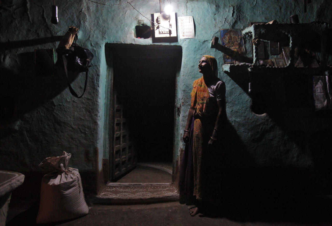 Sampat Bai, 64, poses for a picture inside her house illuminated by a Compact Fluorescent Lamp (CFL) that is powered by solar energy, at Meerwada village of Guna district, in the central Indian state of Madhya Pradesh June 18, 2012. REUTERS/Adnan Abidi