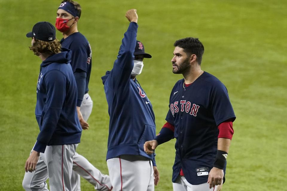 Boston Red Sox manager Alex Cora, center, and J.D. Martinez, right, celebrate the team's 6-1 win in a baseball game against the Texas Rangers in Arlington, Texas, Friday, April 30, 2021. (AP Photo/Tony Gutierrez)
