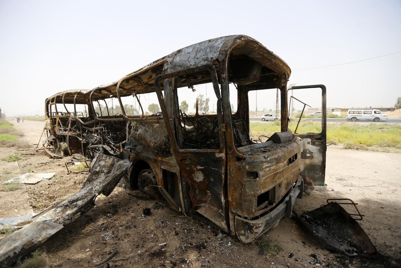 A view of a burnt bus in Taji, north of Baghdad July 24, 2014. A shooting and bombing attack on a bus near Baghdad killed 52 prisoners and nine policemen on Thursday, Ministry of Justice sources said, as politicians faced pressure to form a power-sharing government that can tackle a Sunni insurgency. The bus was transporting prisoners from a military base in the town of Taji to Baghdad when it was hit by roadside bombs, the sources said. Gunmen then opened fire. The attack left a burned shell of the vehicle along a rural road. REUTERS/Thaier al-Sudani (IRAQ - Tags: CIVIL UNREST POLITICS TRANSPORT)