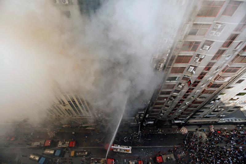 Firefighters work to douse a fire in a multi-storied office building in Dhaka, Bangladesh, March 28, 2019. (AP Photo/Mahmud Hossain Opu )