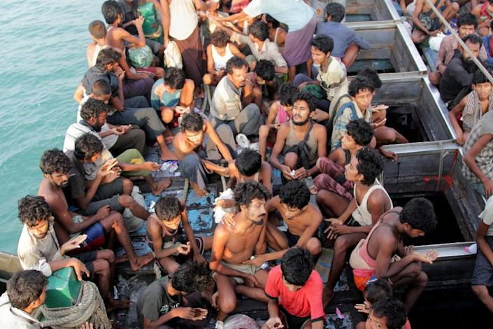 Rohingya migrants sit in their boat as they are towed closer to land by Acehnese fishermen off the coast of Geulumpang in Indonesia's Aceh province, on May 20, 2015 (AFP Photo/Januar)