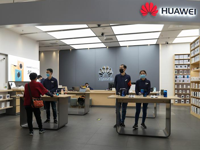 Shop assistants wearing face masks wait for customers in a Huawei store in Beijing, China on February 17, 2020.