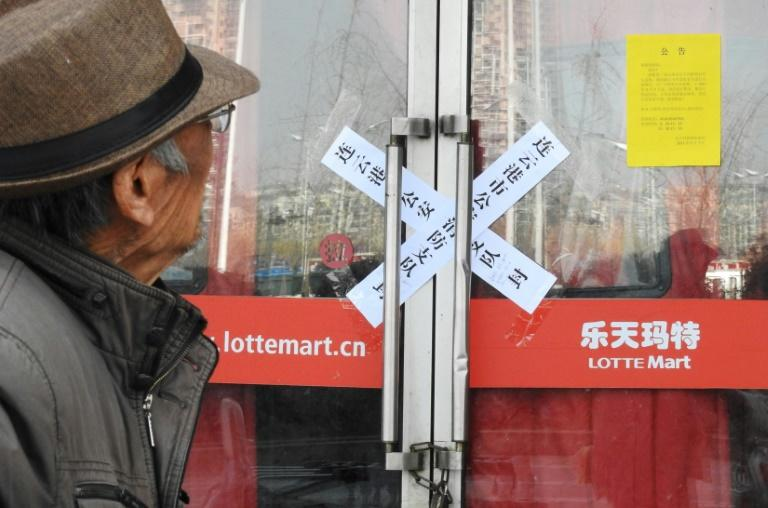 A man looks at the door of a closed Lotte store in Lianyungang in China's eastern Jiangsu province on March 7, 2017
